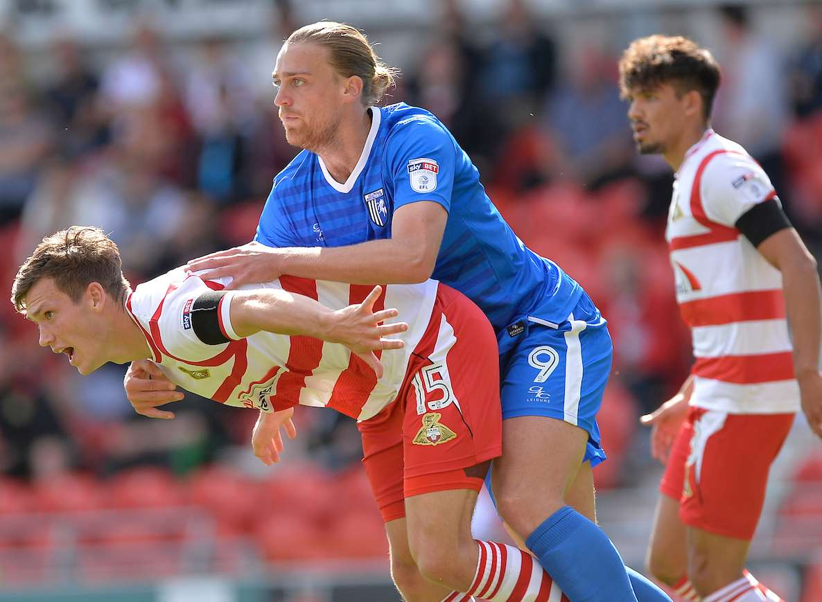 Gillingham striker Tom Eaves up against Doncaster's Joe Wright Picture: Ady Kerry
