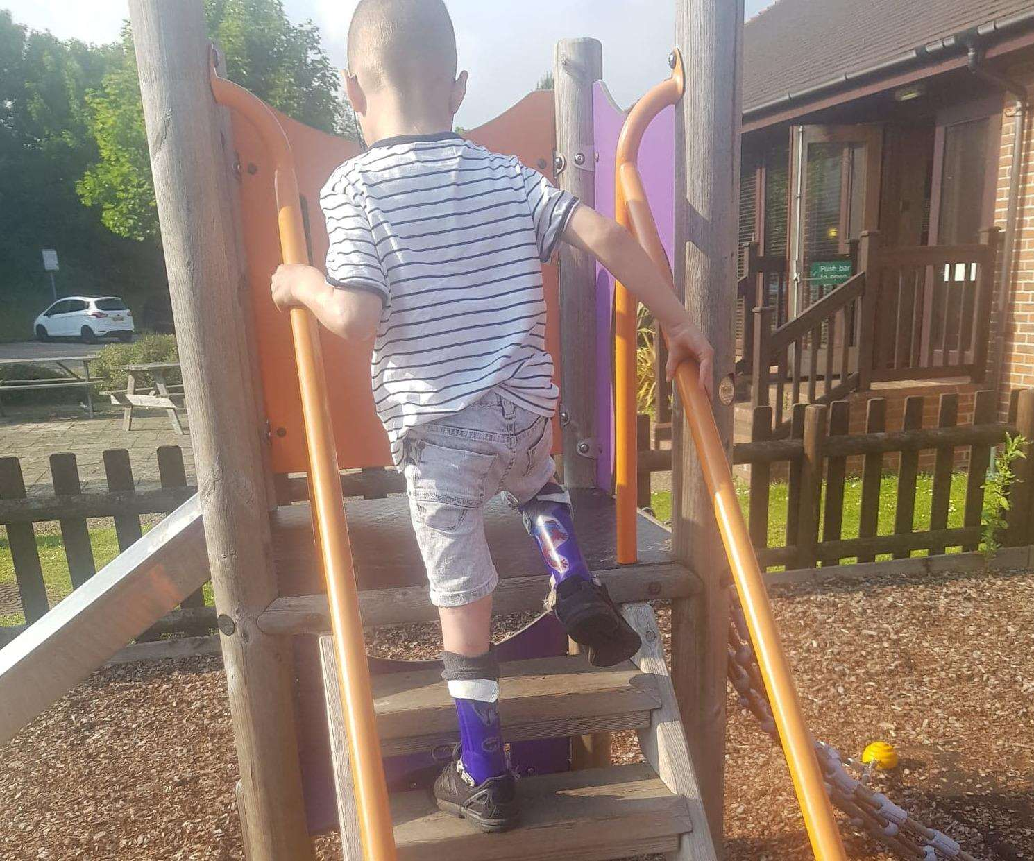 Theo Knott conquers the steps up the slide following his surgery
