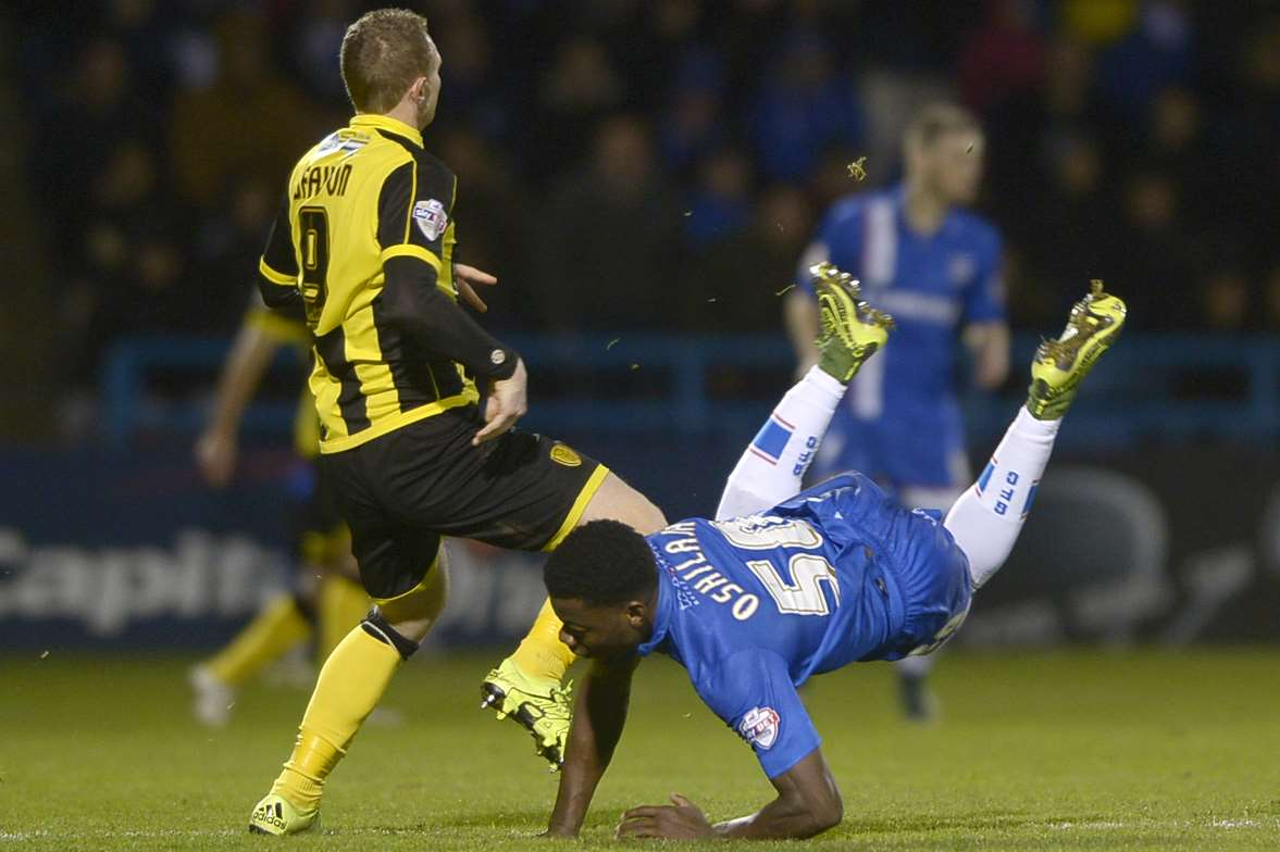 Deji Oshilaja and Gills tumble against Burton at Priestfield Picture: Barry Goodwin