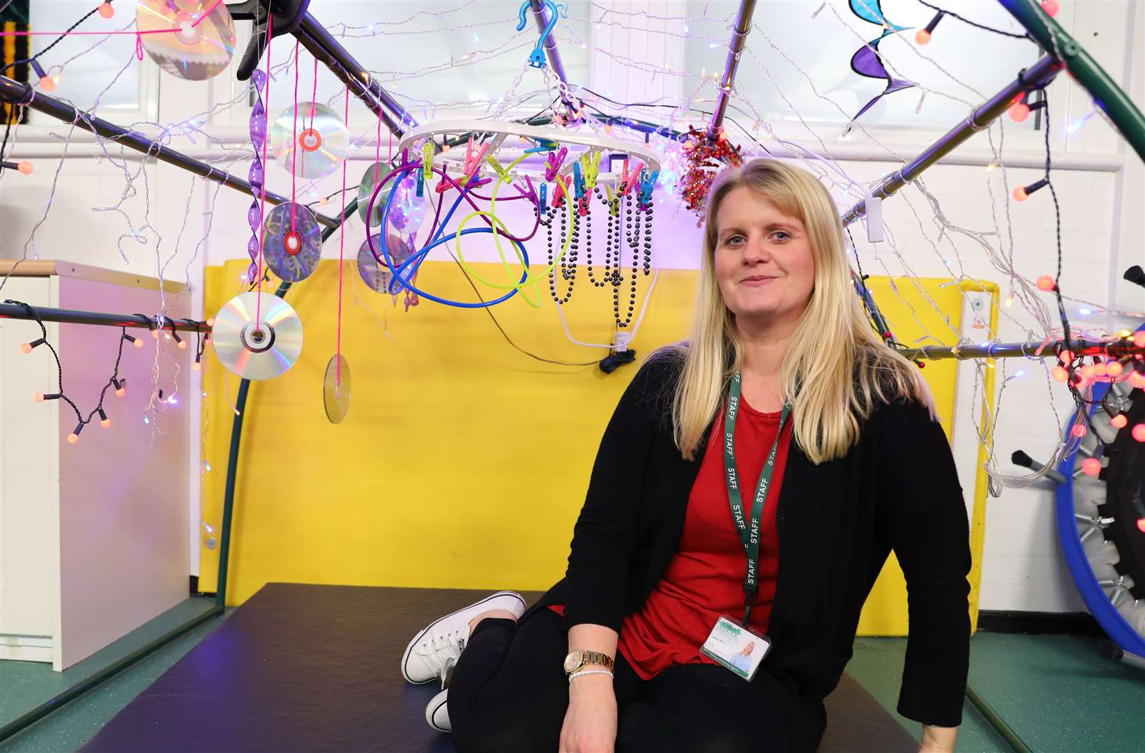 Laura Allen, high level teaching assistant in the Daisy Class, in a display decorated by CDs bought in by teachers