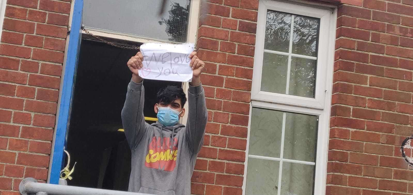 A refugee holds up a 'we love you' sign Picture: Rhys Griffiths