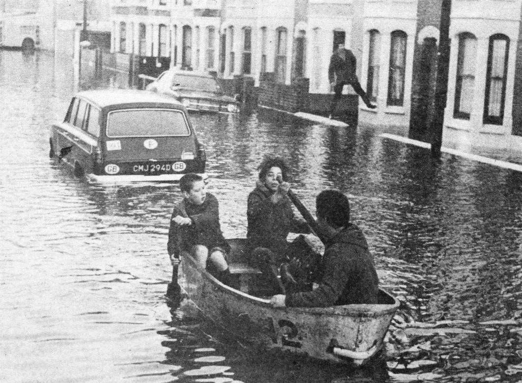 When the car was submerged by water this family in Delamark Road found alternative transport in the form of a dinghy when the sea flooded Sheerness in January 1978. Picture: KM photographer