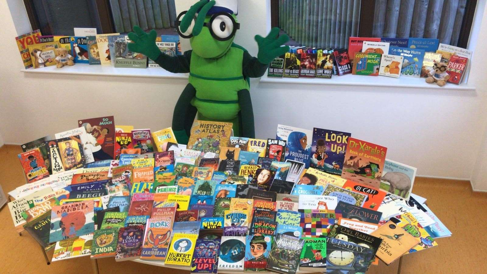 KM Charity Team mascot Buster Bug with the books donated by Scholastic Ltd.