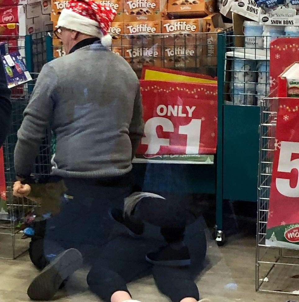A shopworker wearing a festive hat was photographed pinning a person to the floor inside the shop. Picture: Uknip