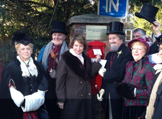 A crowd in 19th century dress at the opening of the post box
