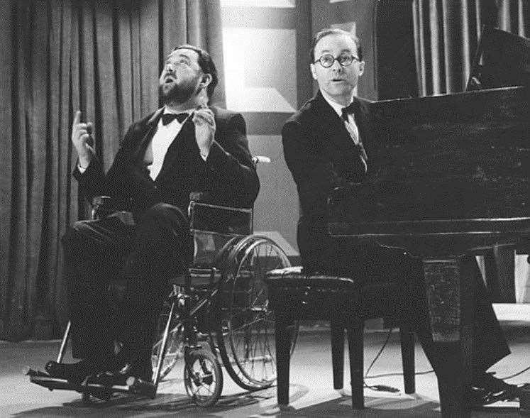 Michael Flanders, left, and Donald Swann at the piano on stage