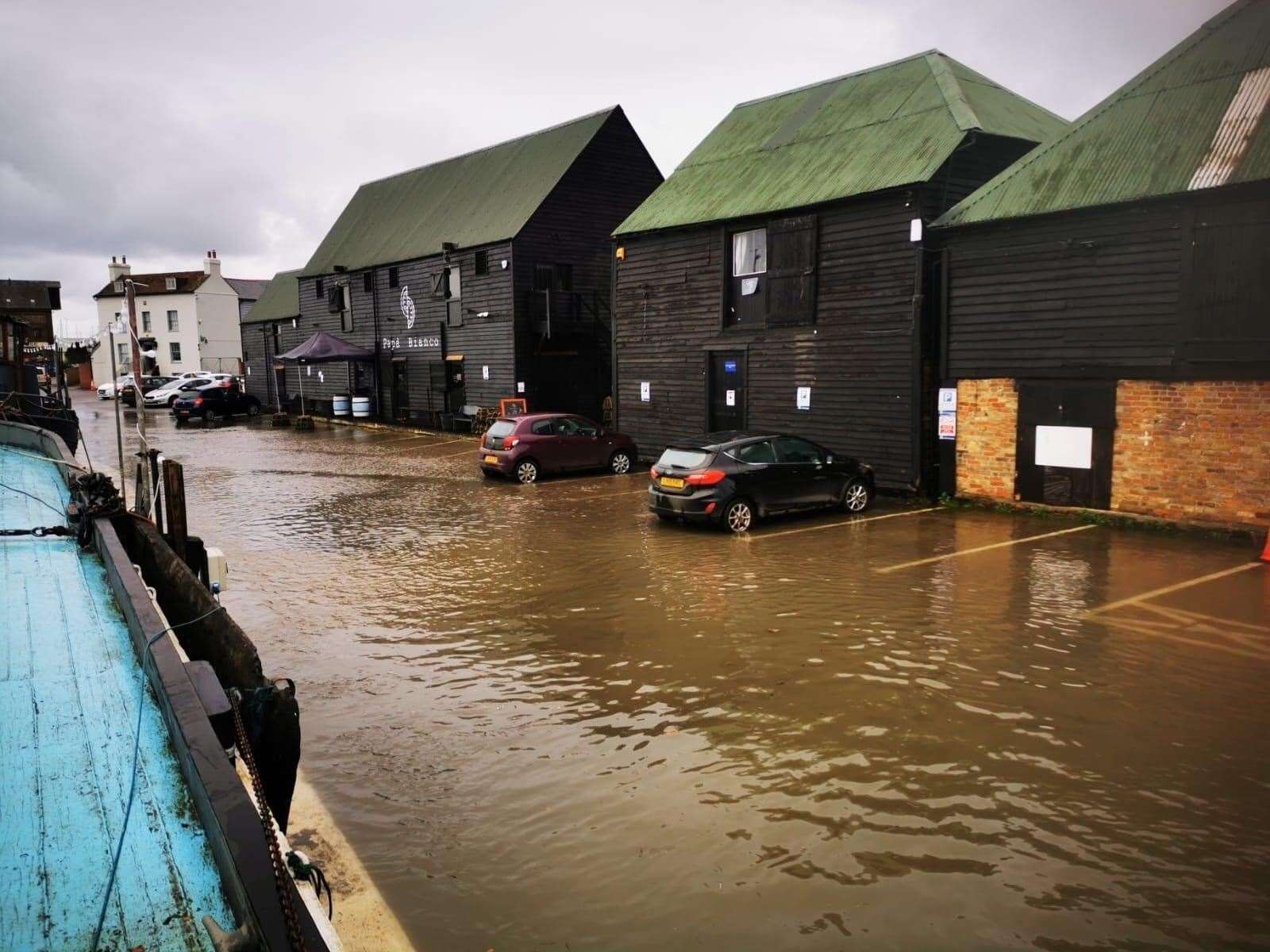 A photo taken earlier this afternoon shows water creeping up to cars and buildings by Faversham Creek. Picture: @GretaBarge1892/Twitter