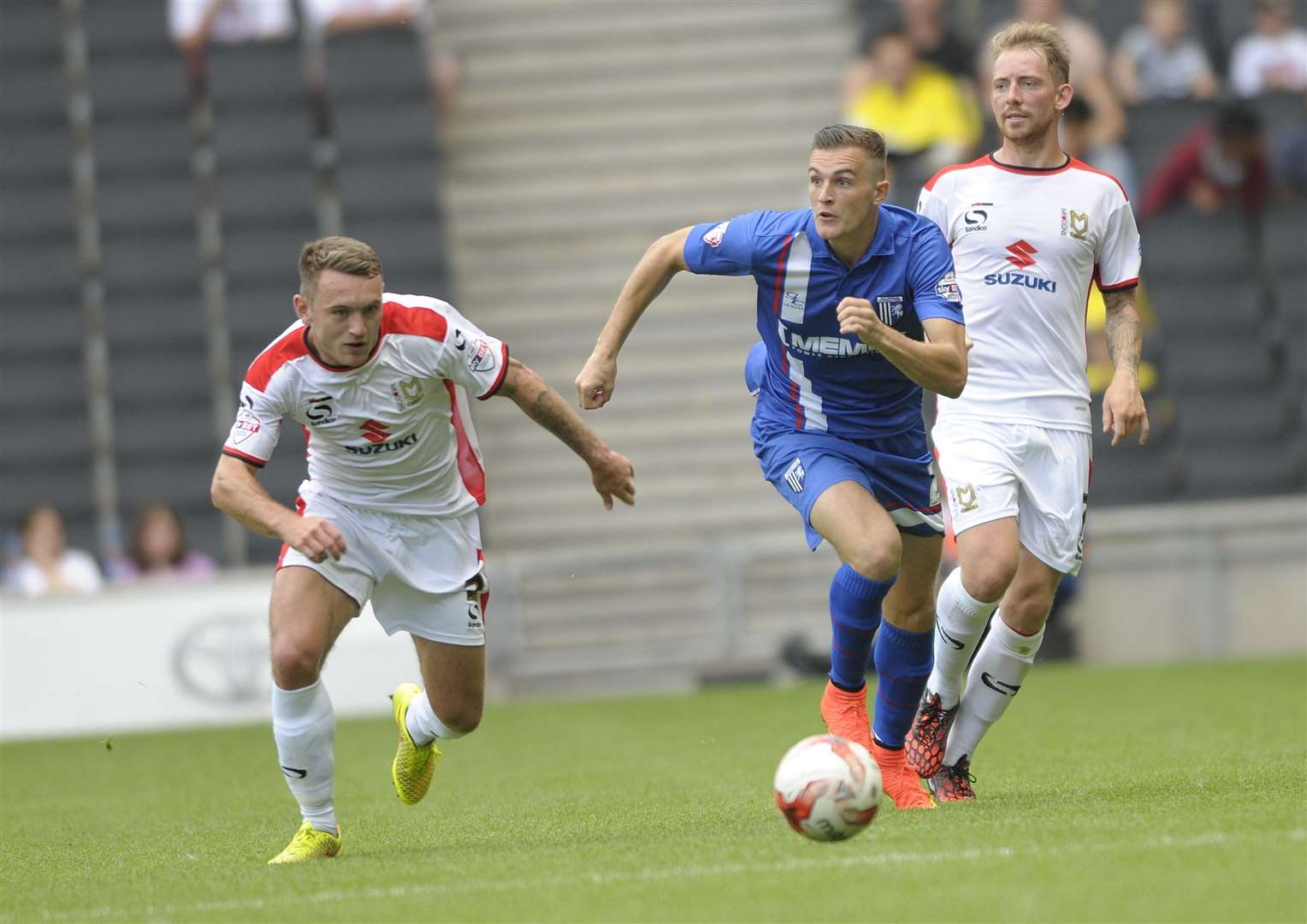 Lee Hodson (left) gives chase when playing against the Gills for MK Dons back in 2014 Picture: Barry Goodwin