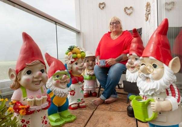 Janet Wilson on her balcony with a collection of cheeky Asda gnomes. Picture: Asda
