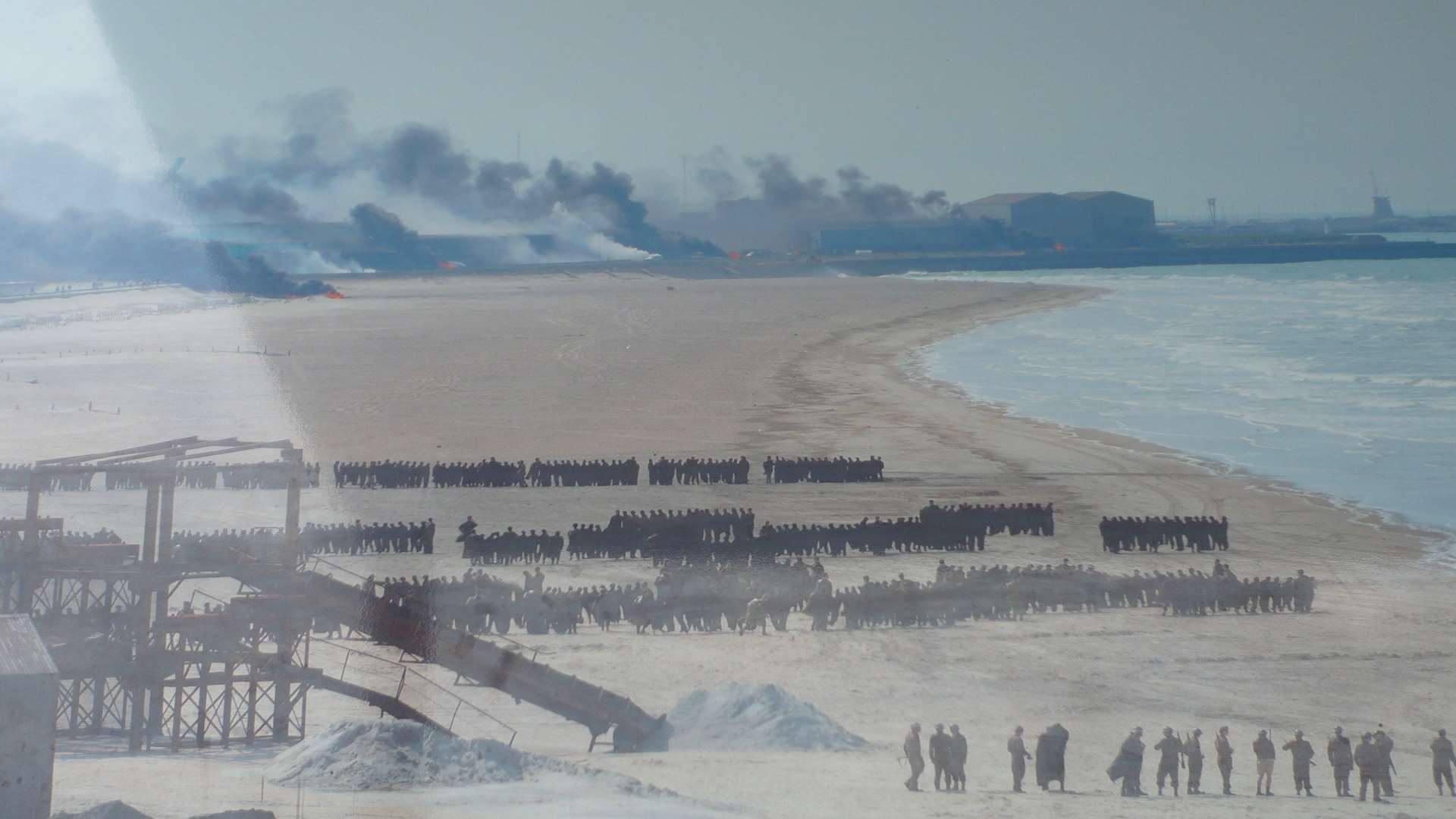 Dunkirk beach was transformed with thousands of extras and factories were made to look on fire for the film.
