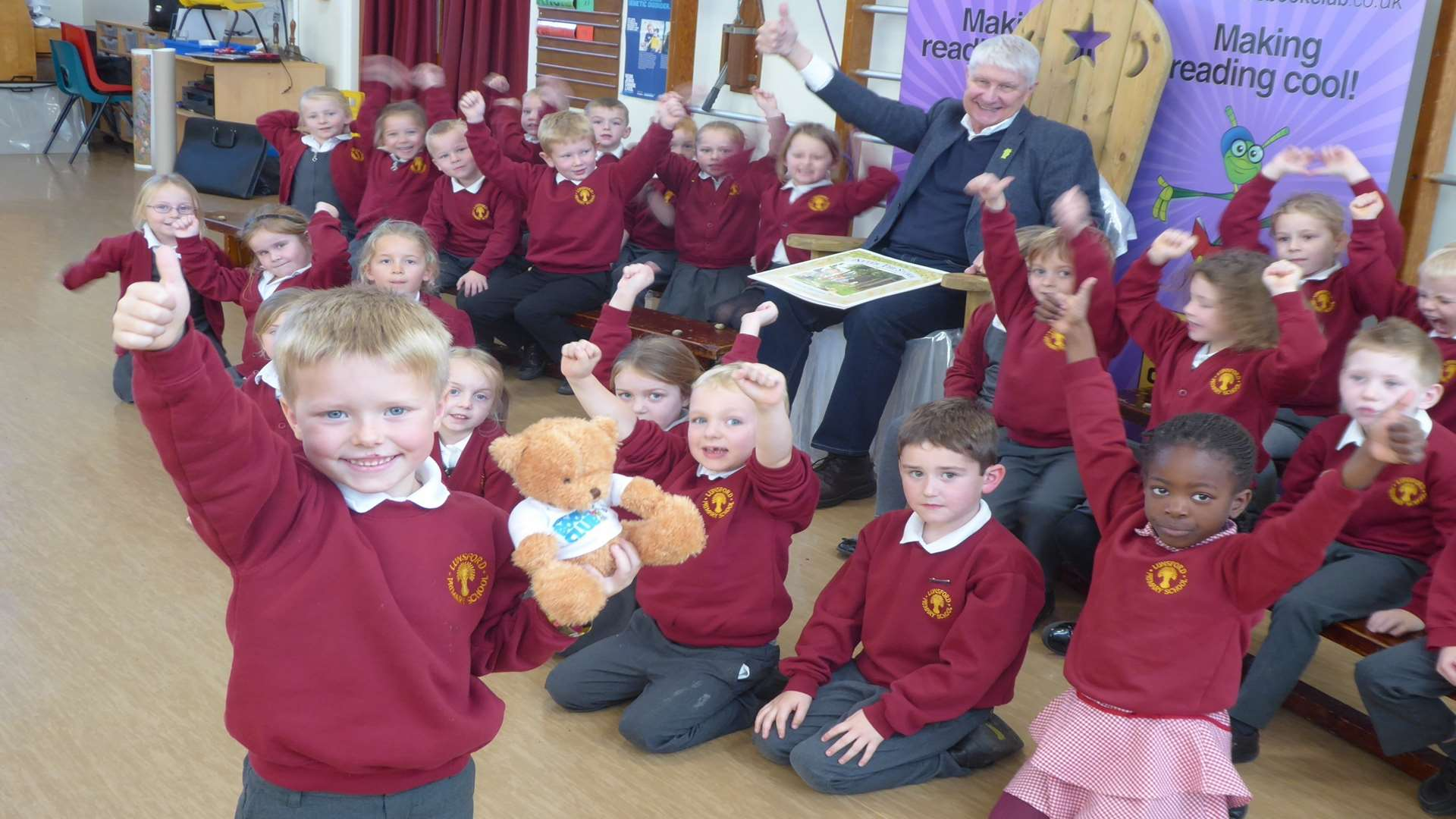 Reiss Coulter, 5, with Buster's mascot Ted cheered on by author and illustrator Nick Butterworth and classmates at Lunsford Primary School, Maidstone. Elephant Class won Kent reading challenge organised through Buster's Book Club.