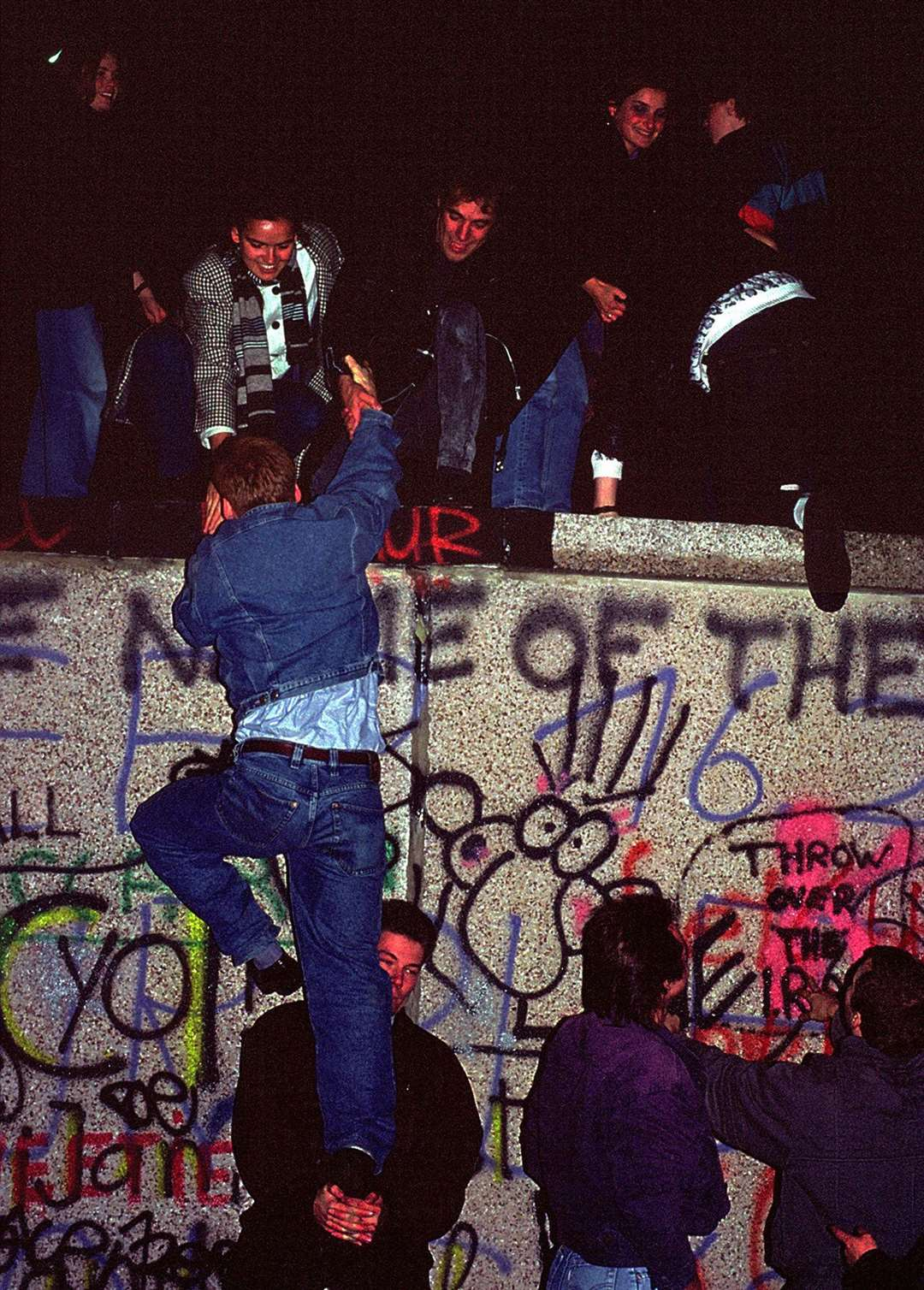 People climbing the Berlin Wall on November 9, 1989. Picture: iStock/PA