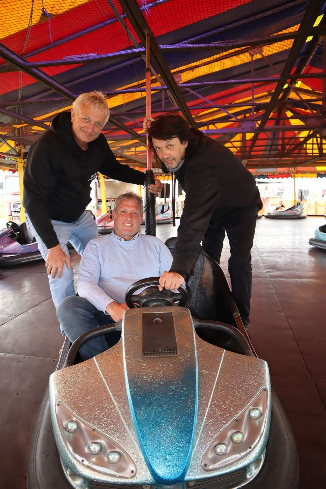 Cllrs Mike Baldock, left, and Richard Palmer give funfair boss Carlos Christian a hand on the dodgems at Smith's funfair at Barton's Point, Sheerness