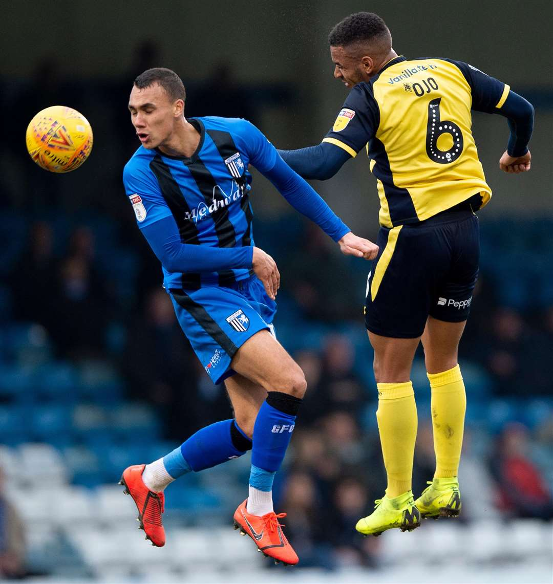 Gills' Graham Burke jumps for the ball with Funso Ojo Picture: Ady Kerry