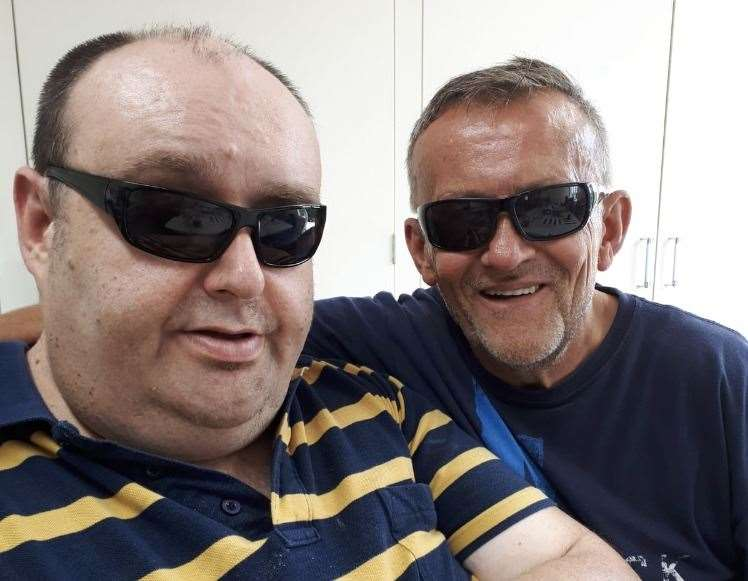Anthony Saw, pictured with his main carer Richard Parsons, has had to stop his 12-week sponsored swim challenge