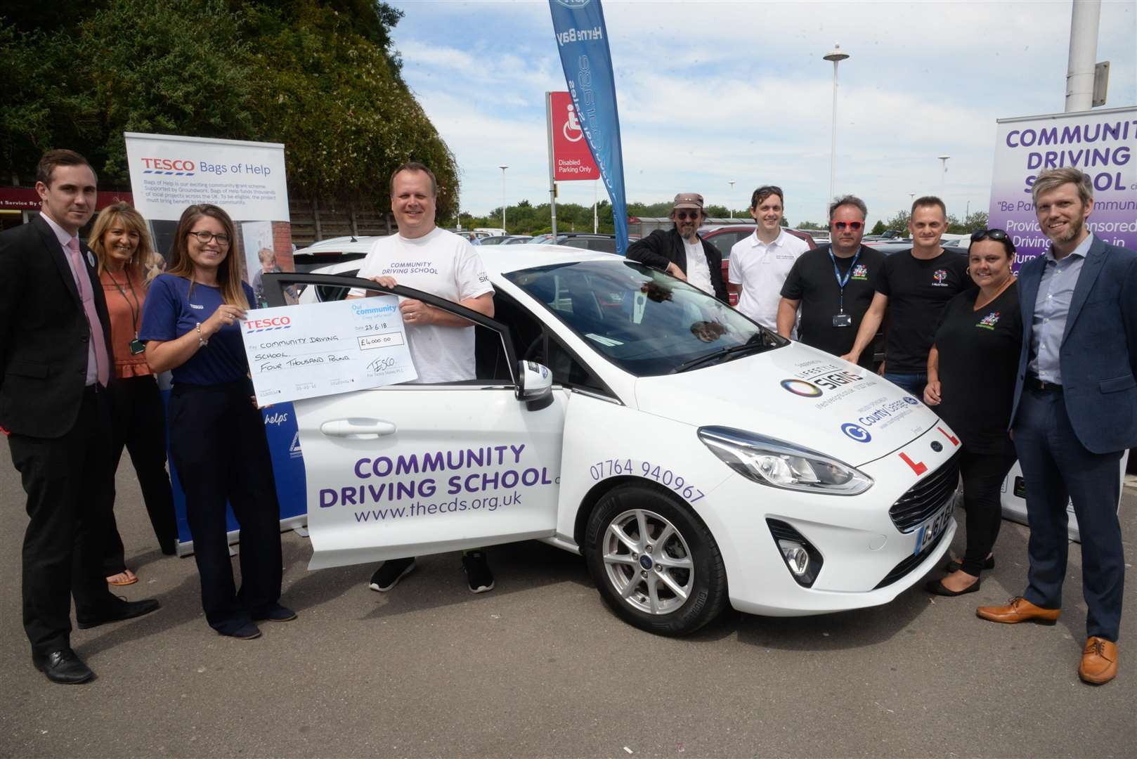 Loisa Dane, Community Champion at Tesco presents John Nicholson with a new car and a cheque for £4000