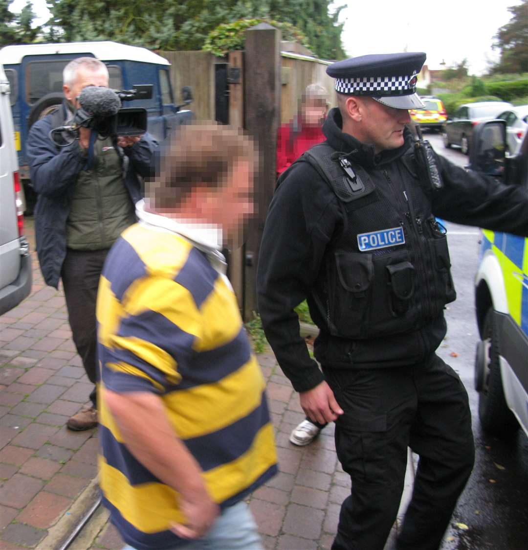 Darrell Houghton being arrested by police during the raid in 2012. No criminal charges were brought in England