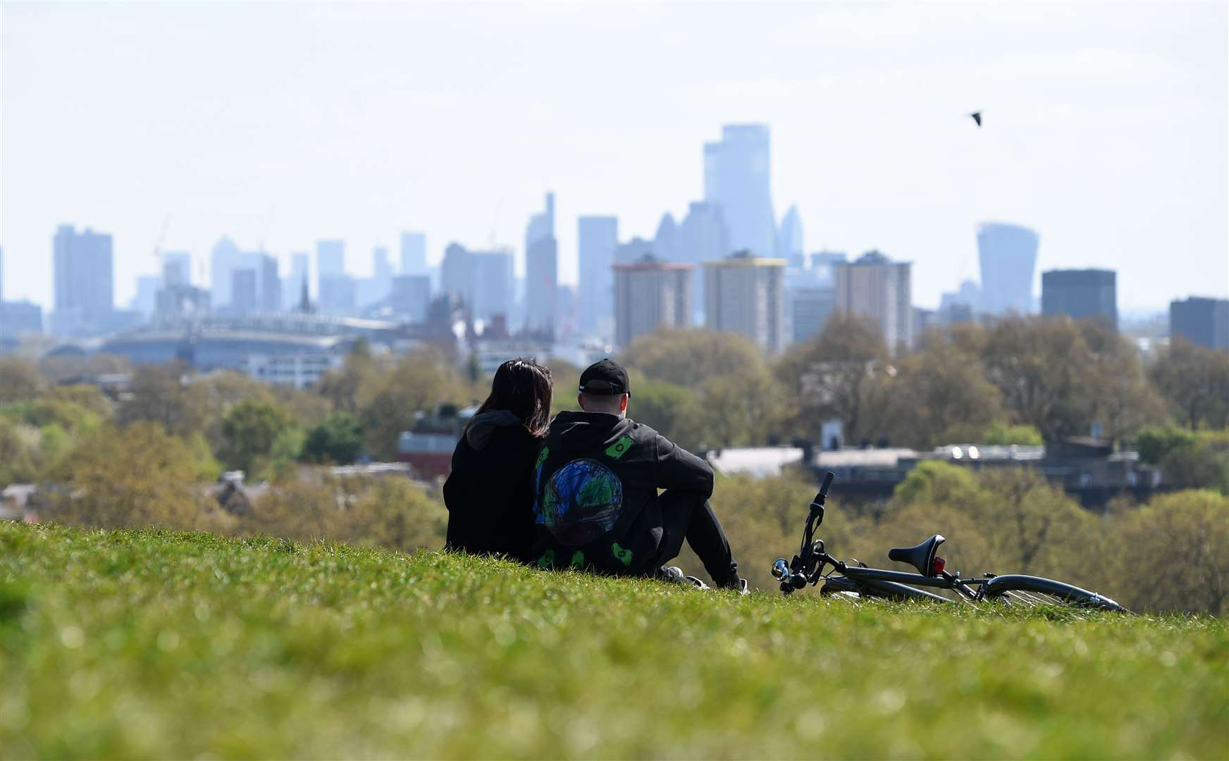 People sit on Primrose Hill, London (Kirsty O'Connor/PA)