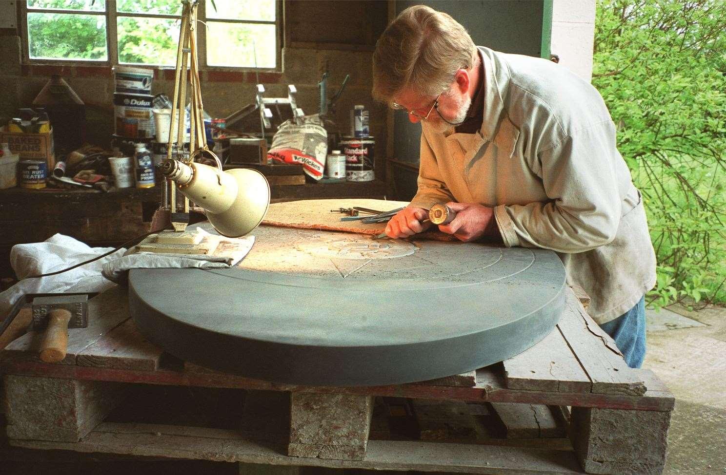 Michael Rust de Hastingleigh termina de esculpir la pizarra de Cumberland Compass Rose que se colocó sobre Wye Crown en 2003