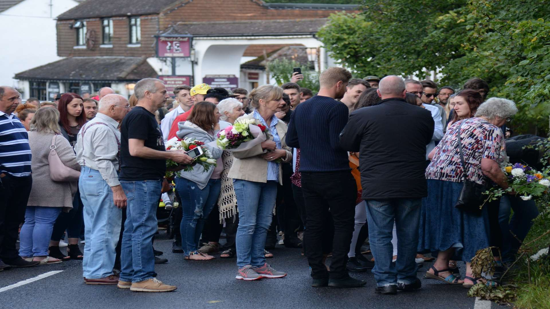 Family and friends laying floral tributes on Canterbury Road, Herne