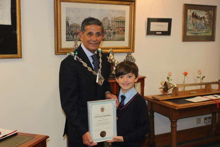 Mayor of Ashford Cllr Winston Michael presents the award to nine-year-old Harrison Cummins