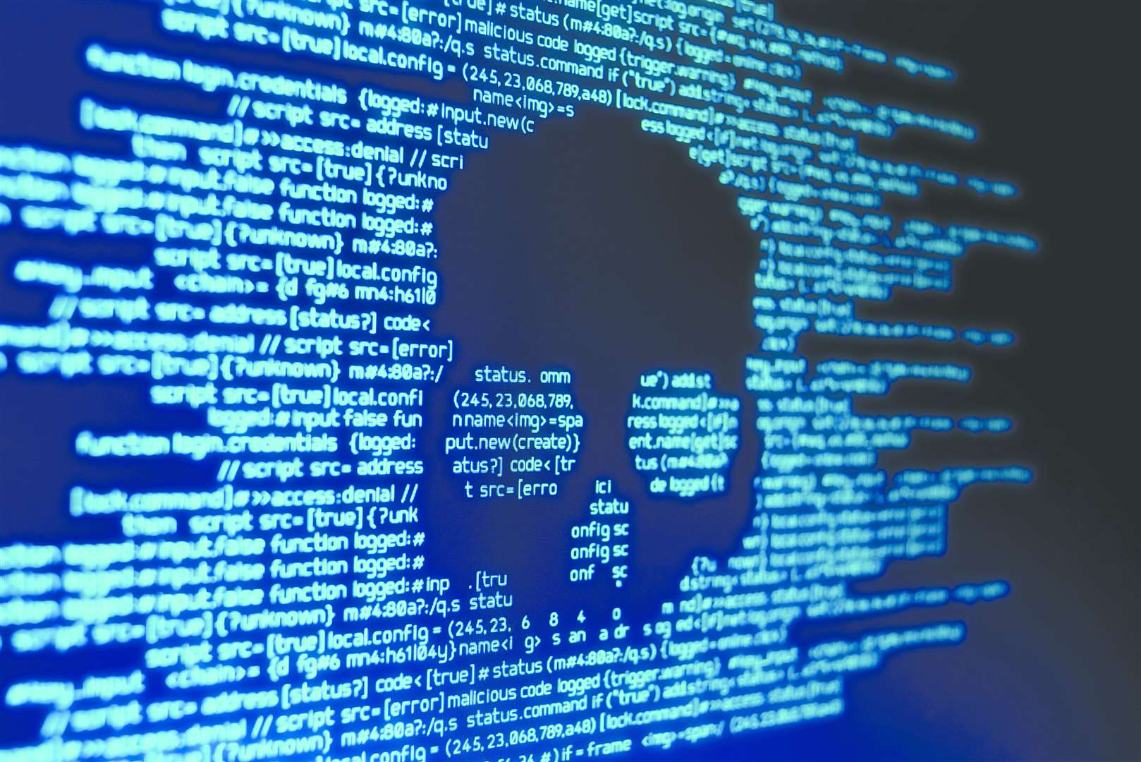 Computer code on a screen with a skull representing a computer virus attack