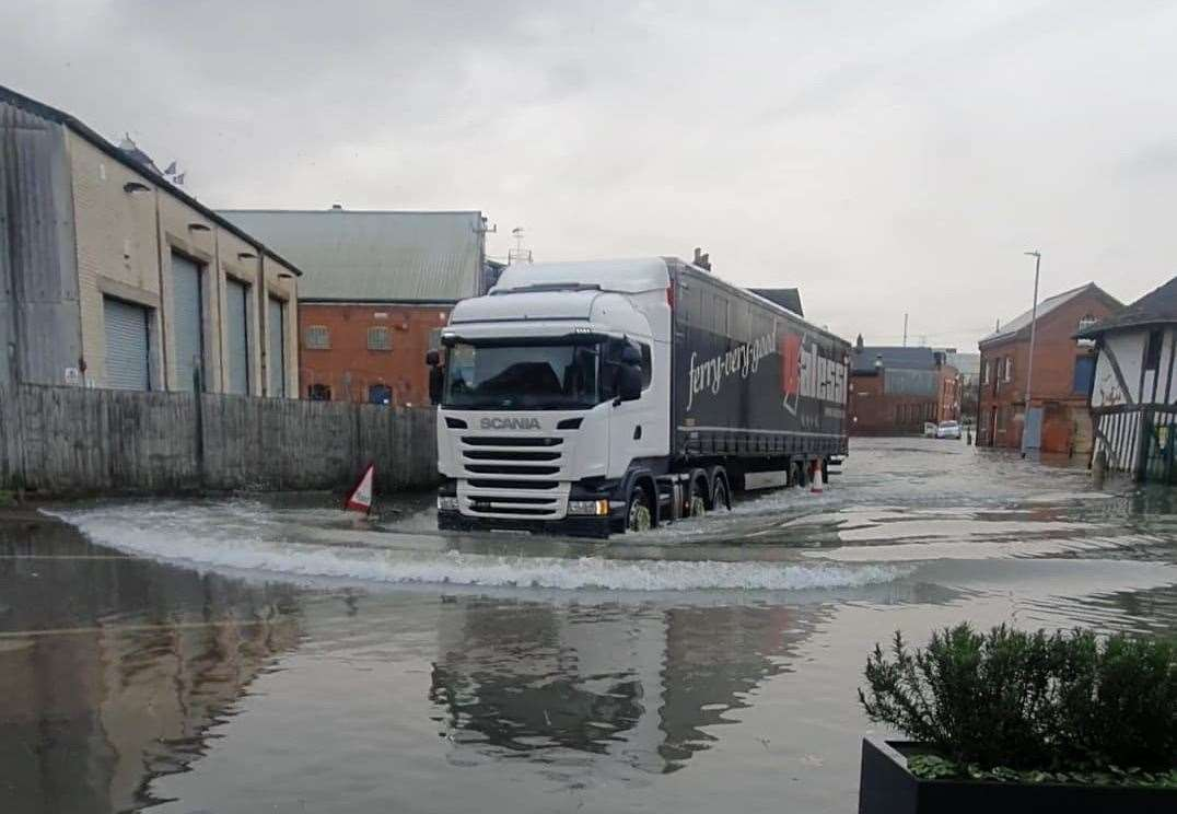 A lorry causes waves as it heads through the Faversham floods. Picture: The Quay