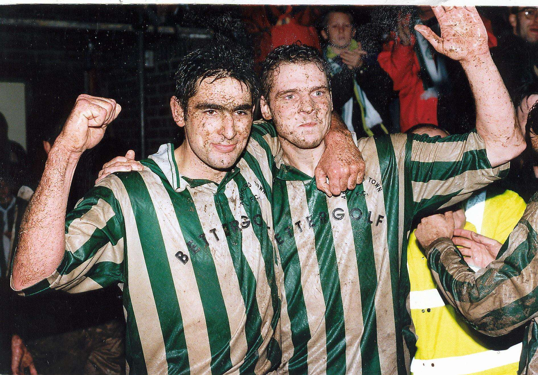 Dave Arter and Nicky Dent celebrate in the mud after Ashford Town's FA Cup home draw with Fulham