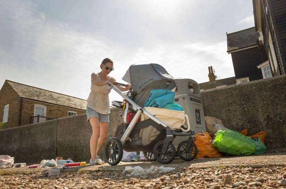 A lady pushes her pram through the litter and debris discarded in Whitstable photo: Tim Stubbings