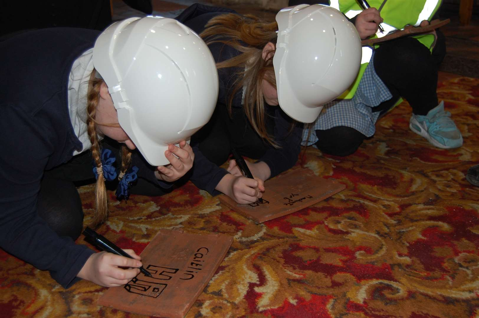 Pupils from Lawn Primary School each sign a tile for the church's new roof.
