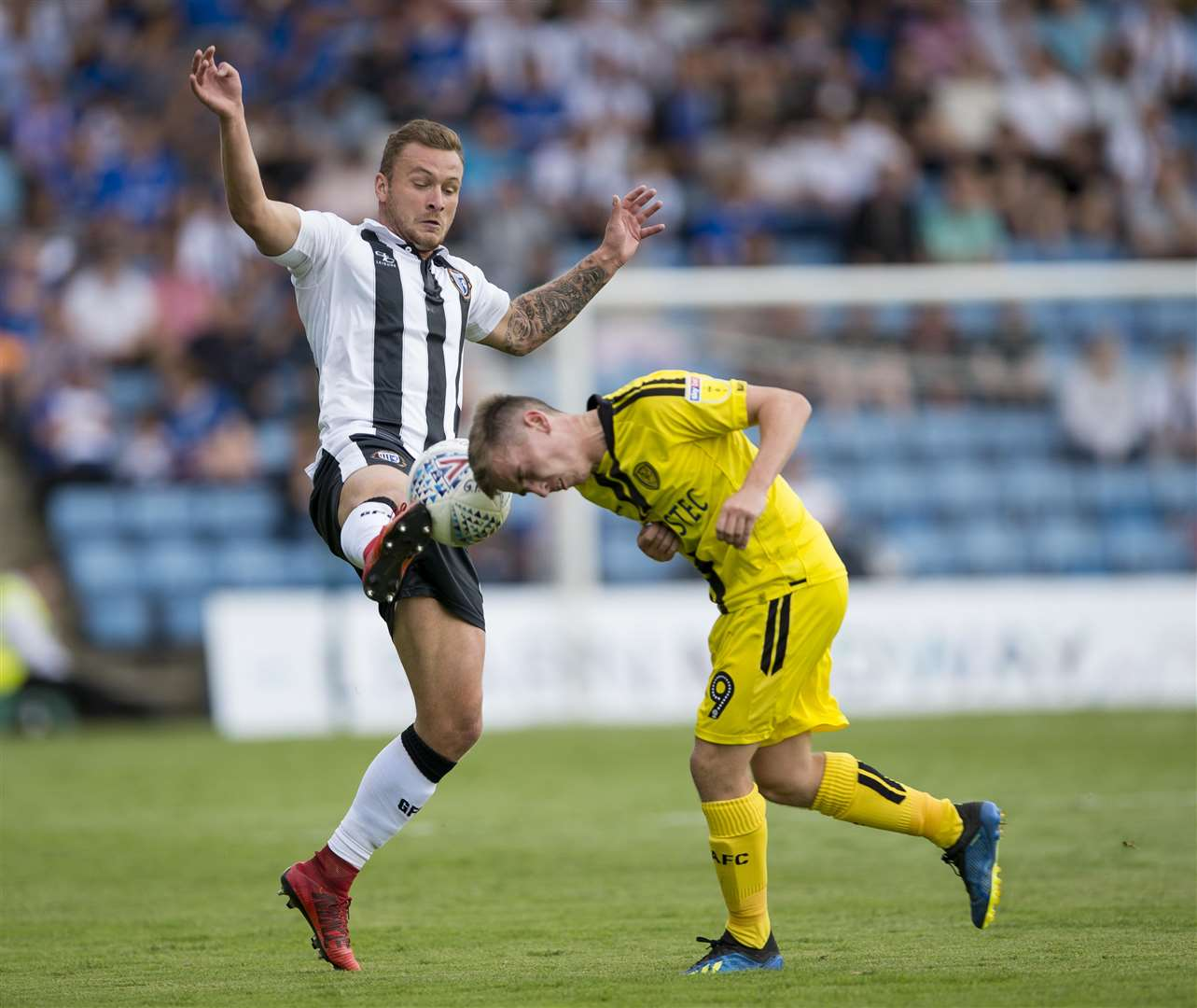 Gillingham's Dean Parrett challenges with Burton's Joe Sbarra. Picture: Ady Kerry