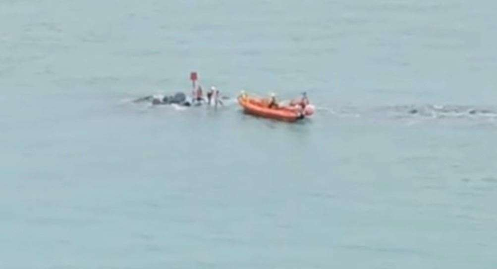 The teenagers were helped off the disappearing rocks two at a time. Picture: FolkestoneFollow on Instagram (14781923)