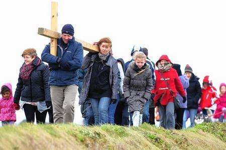 Steve Brown, helped by Tracey Wynn, carries a cross with other members of St Henry and St Elizabeth Roman Catholic Church in Broadway, Sheerness