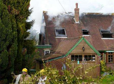 Firefighters at the scene of the house fire in Etchinghill. Picture: Max Hess
