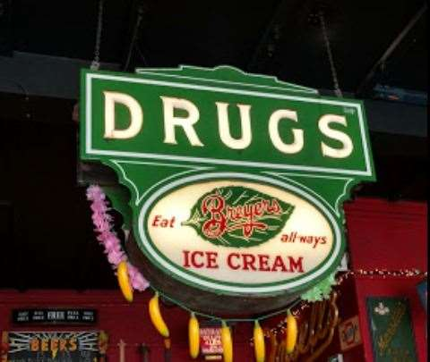 An American drug store sign hangs from the ceiling