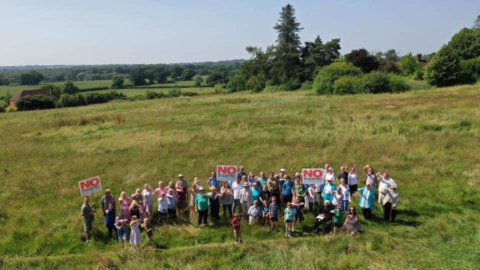 Protesters stand in the fields where homes could be built (13225731)