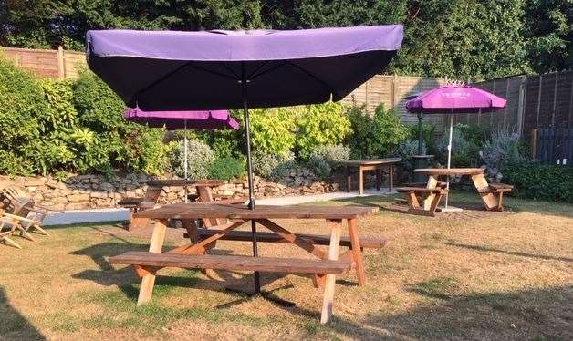 The picnic benches in the well-maintained garden have purple Tribute umbrellas to provide some respite from this summer's strong sunshine