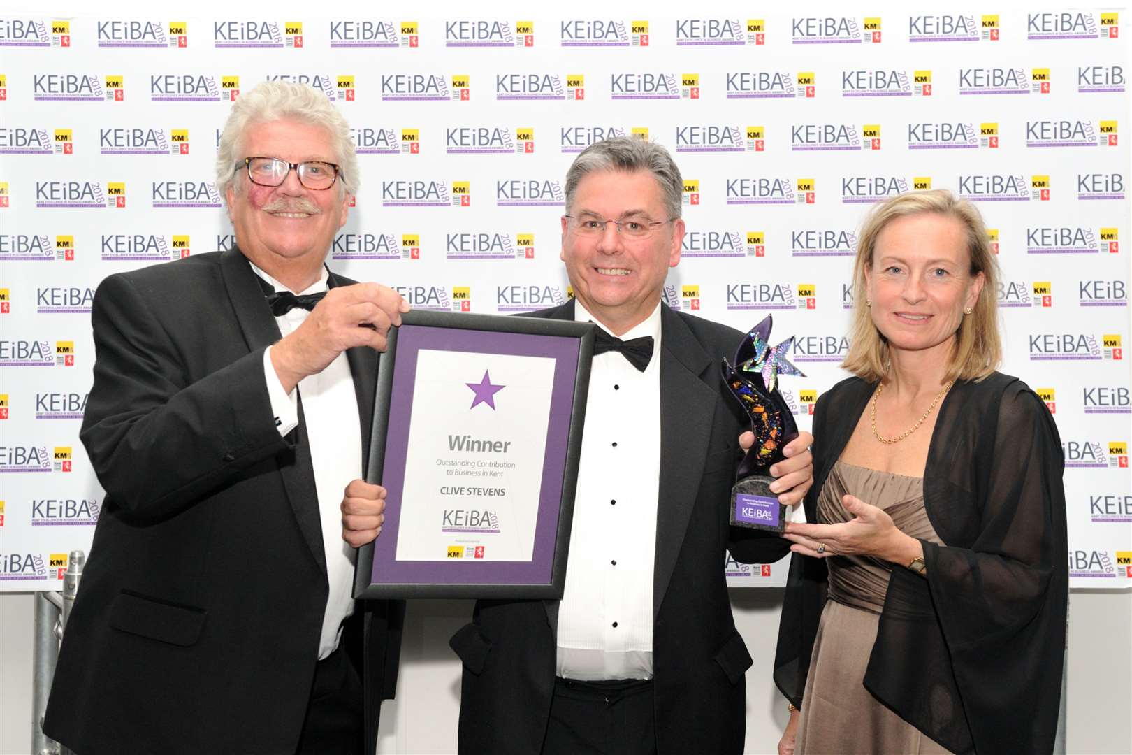 Clive Stevens, centre, wins the Outstanding Contribution to Business Award at KEiBA 2018 - flanked by KCC's Mark Dance, left, and the KM Media Group chairman Geraldine Allinson