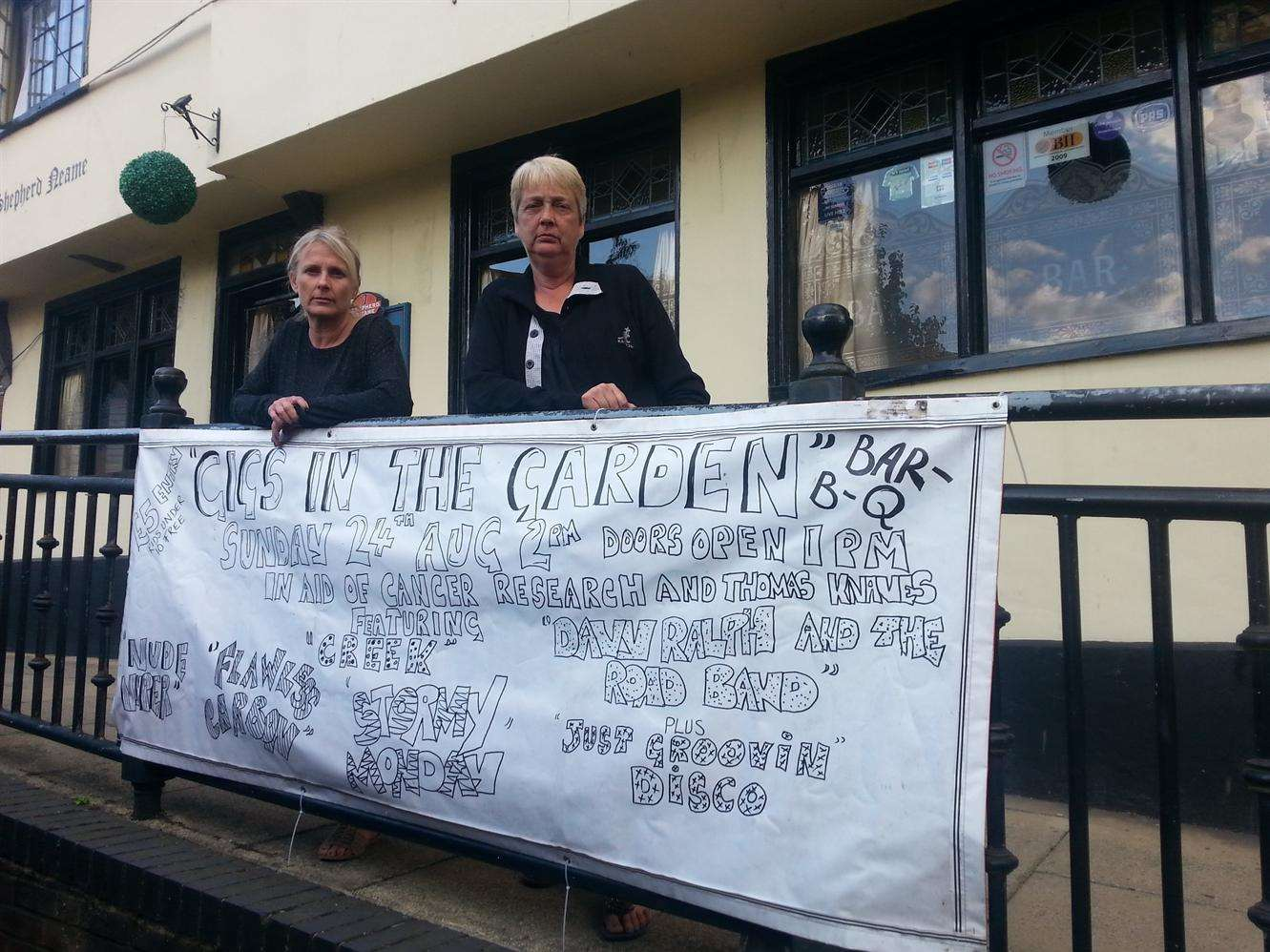 Landlady Sara Apps and regular Julie Knaves next to the banner. Picture: Bess Browning