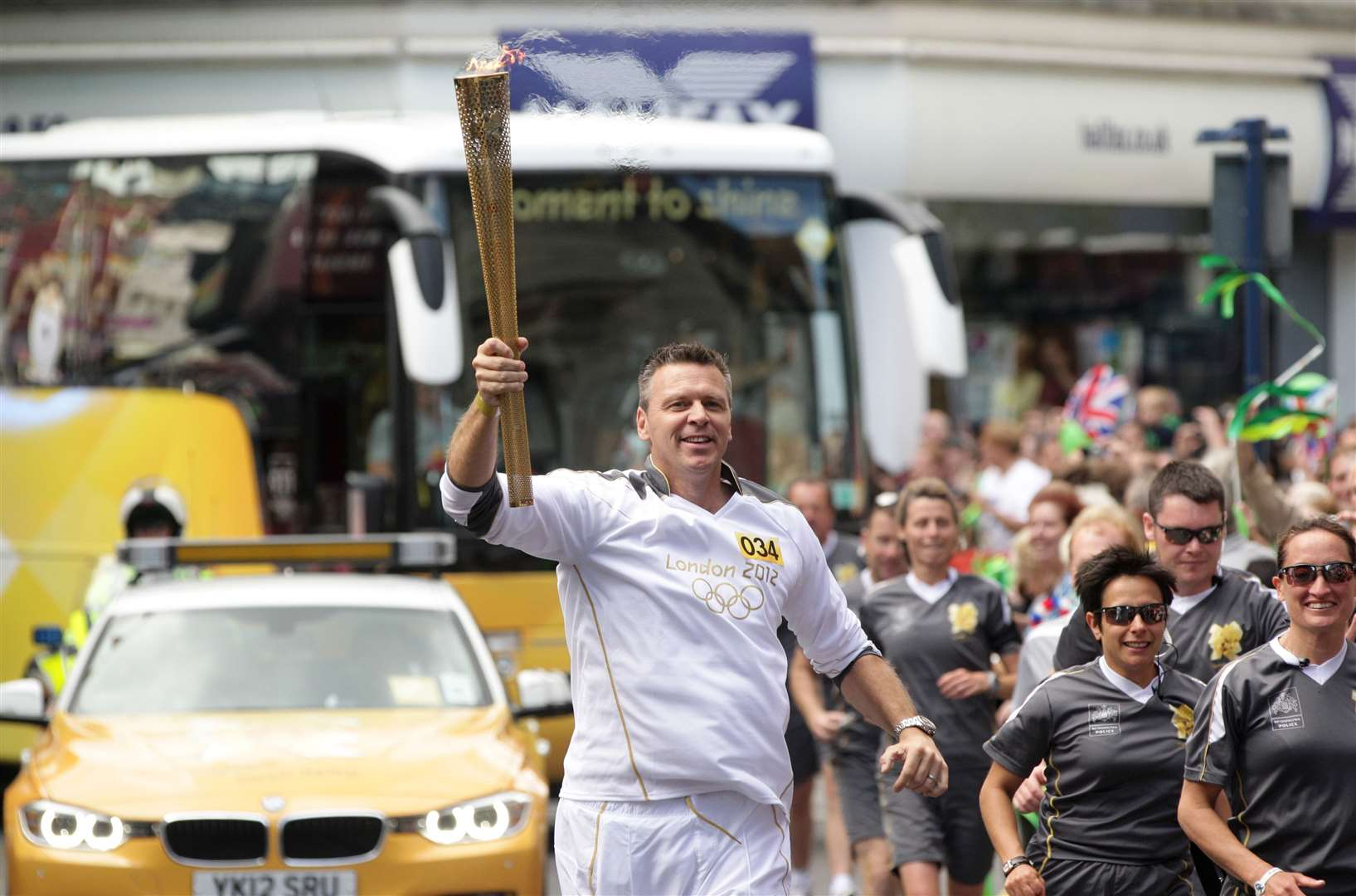 Former Olympian Steve Backley carries the flame at Ramsgate. Pic: Locog
